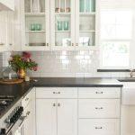 Armoires de cuisine blanches avec comptoirs noirs