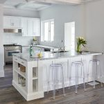 Backless acrylic stools sit in front of a white kitchen peninsula accented with ...
