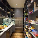 Contemporary gray pantry features a wall of floor to ceiling shelves facing gray...