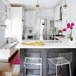 Contemporary tuxedo kitchen features two acrylic bar stools sat in front of a bl...