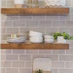 Floating natural wood shelves against a subway tile backsplash makes a perfect m...