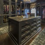 Glam black closet features a black closet island adorned with brass pulls topped...