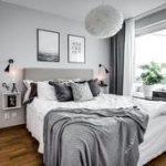 Grau-weißes Schlafzimmer mit Kuscheldecken und Bildern über dem Bett.    Inter...