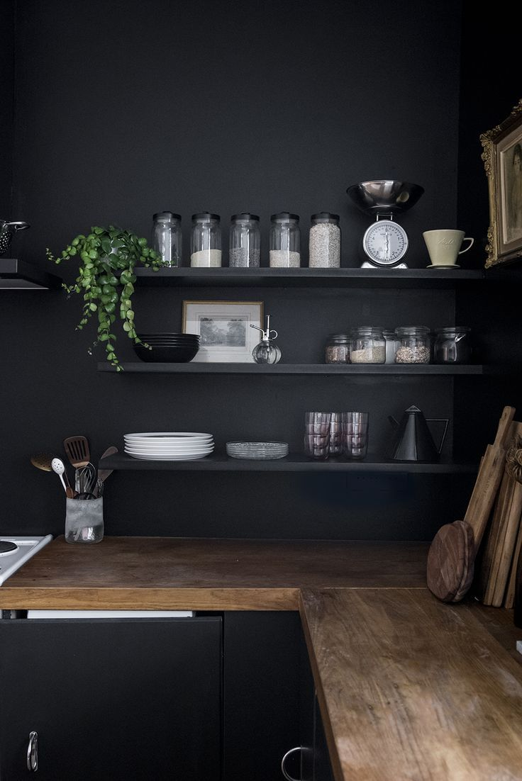 Halloween style!! Dark kitchen walls and cabinets with medium toned wood counter…