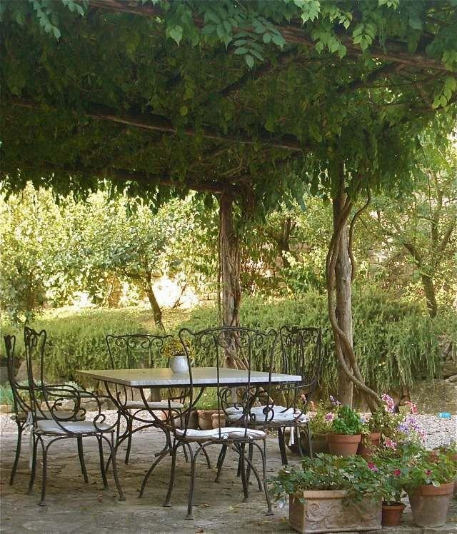Pergola garden climbing plants greenery wrought iron furniture