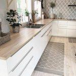 Suelo de tarima claro, con muebles de cocina blancos. Decoración de cocina