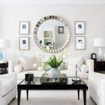 Symmetrical Grouping of Art Surrounding Large Mirror  from BHG via Centsation