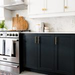 White kitchen uppers mixed with inky black base cabinets warmed with matte brass...