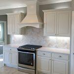 White kitchen with satin nickel fixtures, pendant lights, travertine backsplash,...